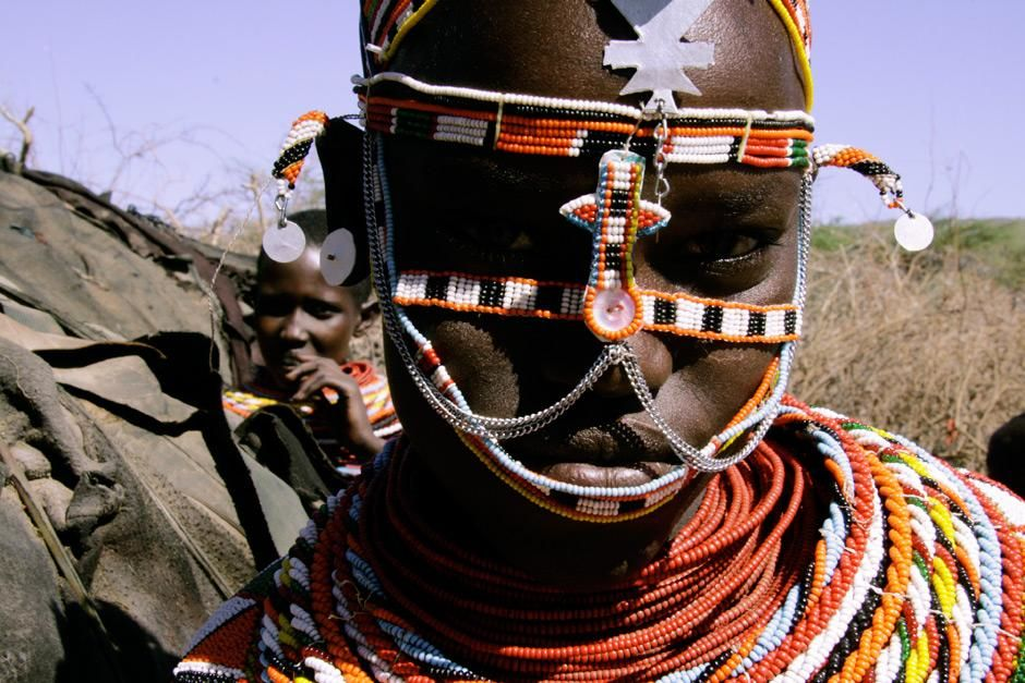 Kenya: A Samburu girl in traditional dress inside her village.