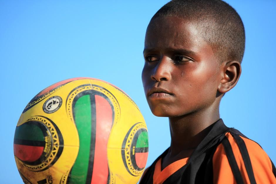 Somalia: A close-up of a Somali boy holding up a football while his eyes catch something outside... [Photo of the day - 十月 2012]