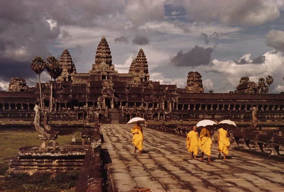 Buddhist monks in yellow robes walk on the main road by the temple in Angkor Wat. Cambodia. [Photo of the day - October 2011]