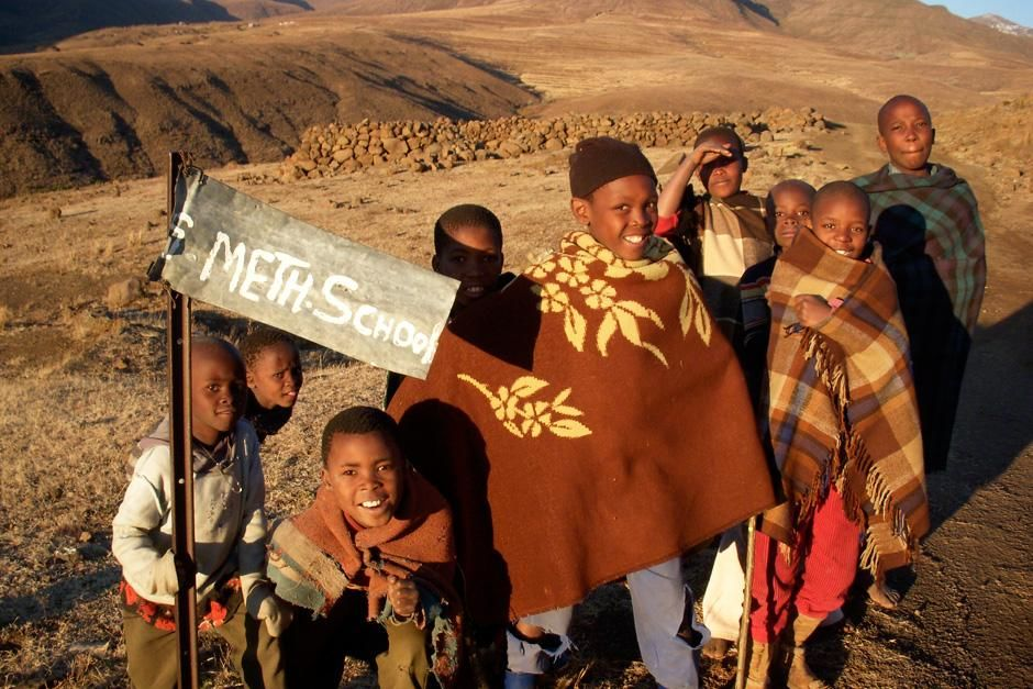Young Basotho children in Africa gather around a sign for their school. This image is from... [Photo of the day - نوامبر 2012]