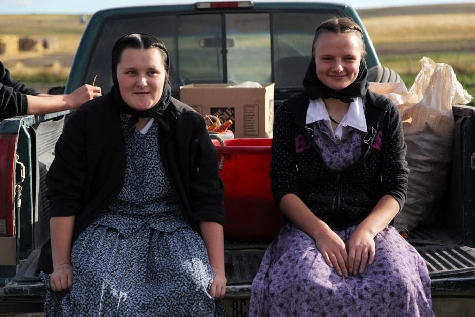 King Colony, Montana: Lori Hofer and Megan Hofer sitting on the back of a truck on carrot picking... [Photo of the day - December 2012]