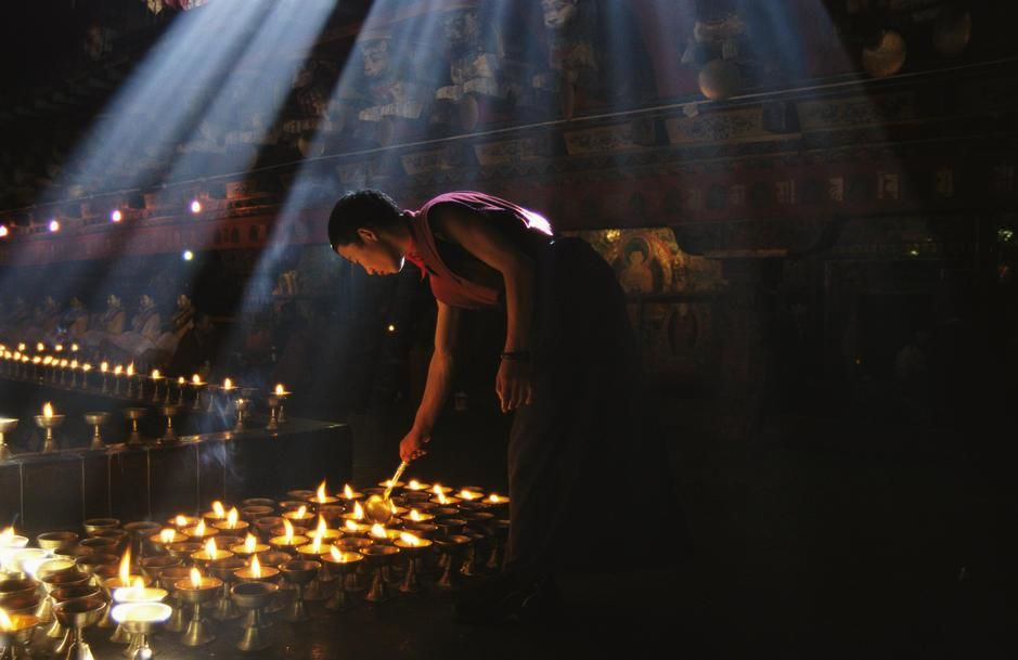 Un moine bouddhiste allume des lampes de dévotion à l'intérieur du temple de Jokhang, Lhasa. T... [Photo of the day - octobre 2011]