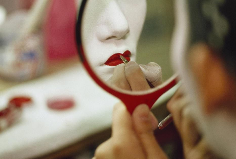 A geisha looks into a mirror to apply red lip colour to her mouth in the Hanamachi or Geiko distr... [Photo of the day - October, 2011]