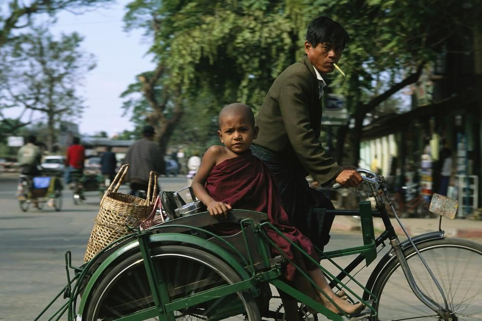 A young Buddhist monk riding in a cab on a bicycle. Myanmar. [Dagens billede - november 2011]