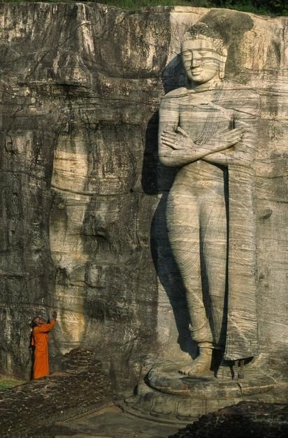 Buddhist monk at the foot of a tall stone Buddha sculpture on a hill. Sri Lanka. [Fotografija dneva - november 2011]