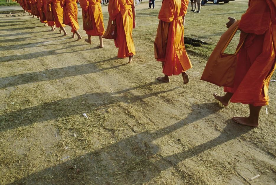 A group of Buddhist Monks walk single file down a dirt road. Thailand. [Photo of the day - juli 2011]