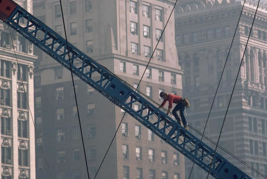 A construction worker climbs up a crane near tall buildings in Pittsburgh, Pennsylvania. USA. [Fotografija dneva - november 2011]