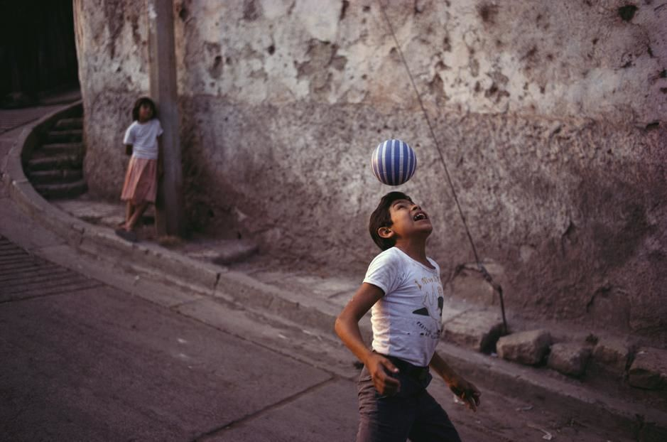 A young girl watches a boy demonstrate his soccer skills in Tegucigalpa. Honduras. [Fotografija dneva - november 2011]