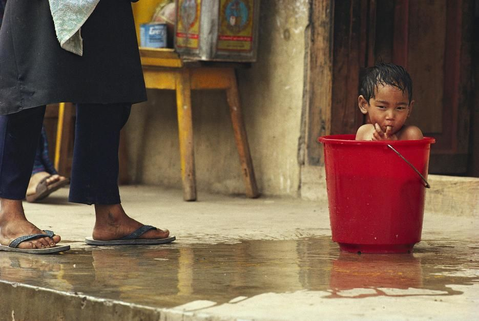 Bhutanese boy bathing in a bucket, Paro. Bhutan. [Dagens billede - november 2011]