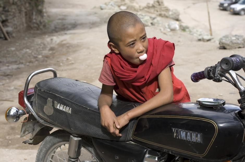 A young monk blows a chewing gum bubble leaning on a Yamaha, Hemis Monastery, Ladakh District. [Dagens billede - januar 2012]