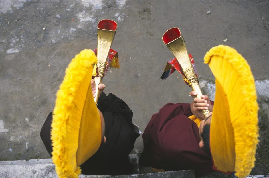 Monks in yellow hats blow horns at a fire puja at Nechung Monastery, Dharmsala. [Dagens billede - januar 2012]