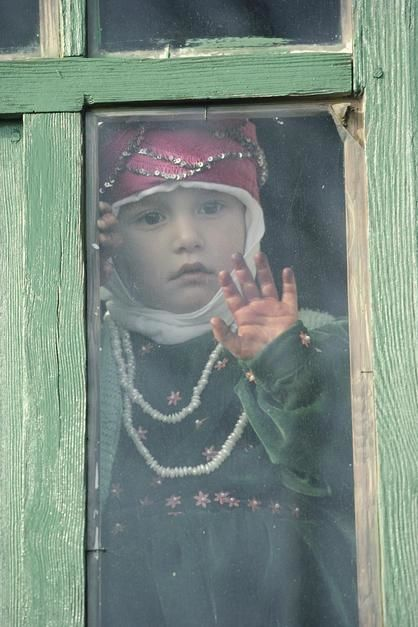 A young Turkish girl looks out of a window in Sogut Golu. [Foto do dia - Janeiro 2012]