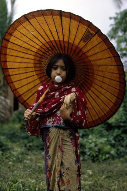 A Muslim girl in traditional dress blows a bubble with her gum. [Foto do dia - Fevereiro 2011]