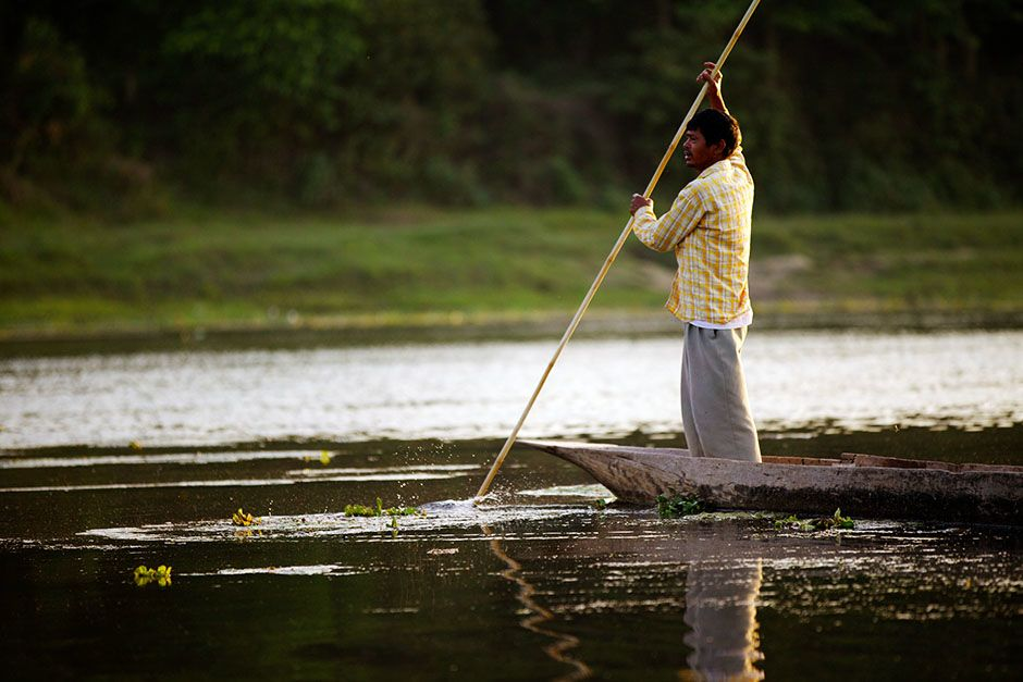 A Ferryman poles a dugout canoe across the Rapti River on the edge of Chitwan National Park.... [Photo of the day - January 2014]