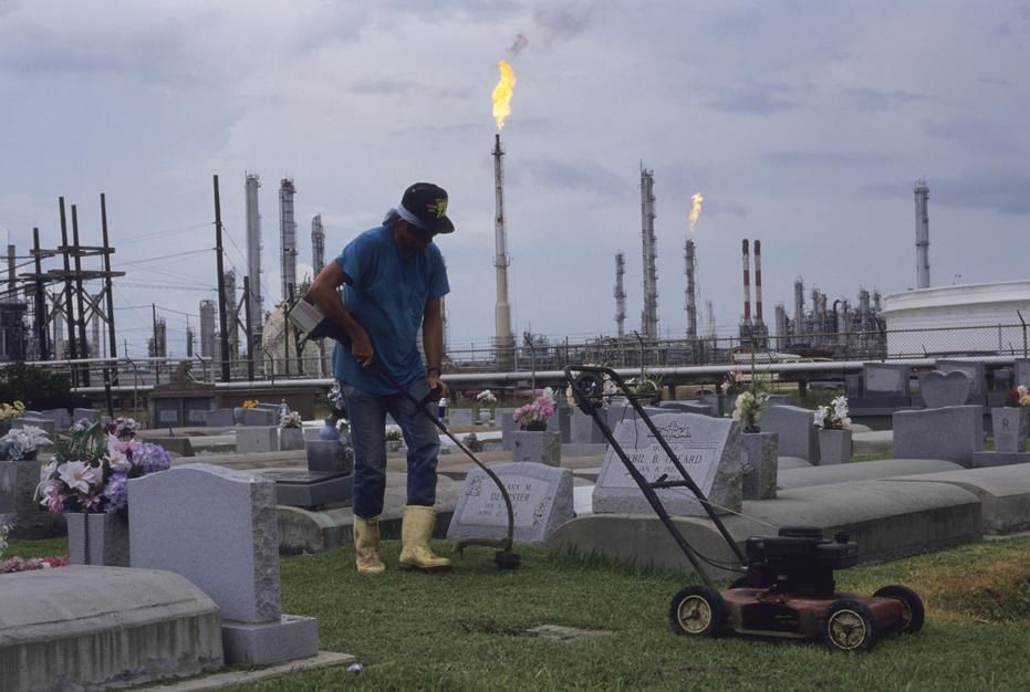 A man cuts the grass at a cemetary in an area known as Cancer Alley in Morrisonville, Louisiana. [תמונת היום - פברואר 2011]