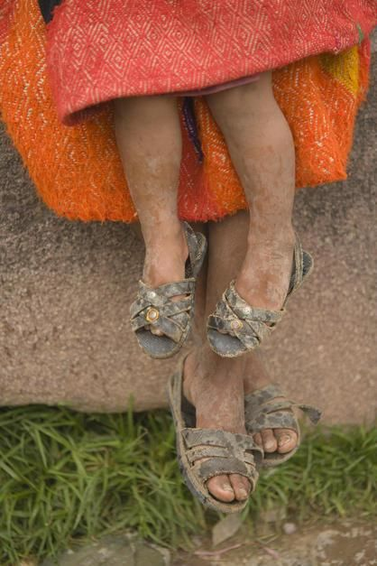 Feet of a Peruvian mother and child in native clothing in Ollantaytambo, Sacred Valley. [תמונת היום - פברואר 2011]