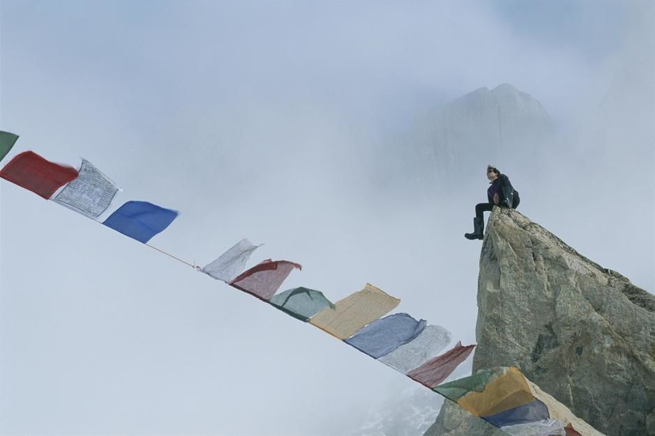 Mountain climber Alex Lowe sits on a rock near Tibetan prayer flags on Baffin Island. Canada. [Dagens foto - augusti 2011]