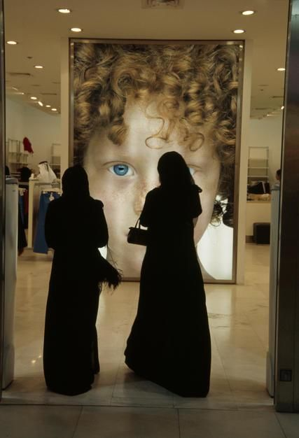 Two veiled Arabic women face an advertising poster in a shopping mall in Doha. [תמונת היום - מרץ 2011]