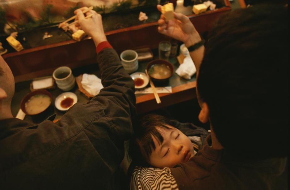 A man holds his sleeping son while eating at a sushi restaurant in Tokyo. [Photo of the day - مارس 2011]