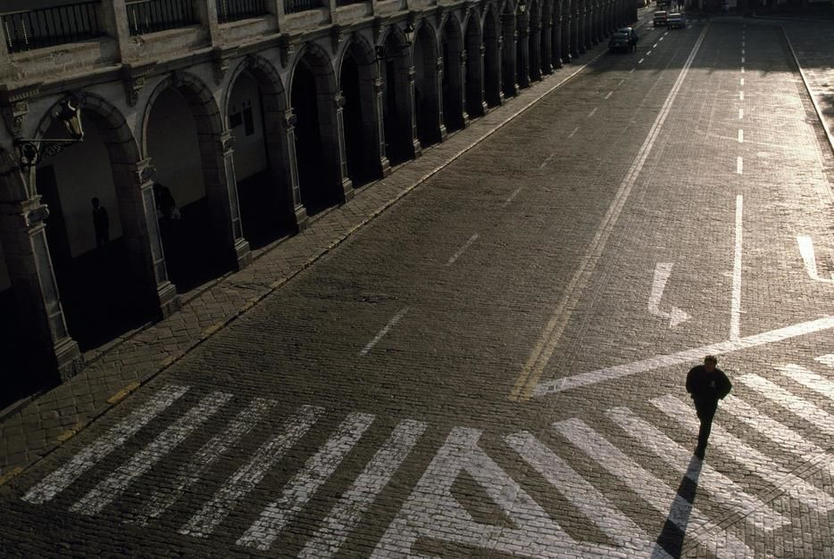 A man crosses the cobblestones of the Plaza de Armas in Arequipa. [תמונת היום - אפריל 2011]