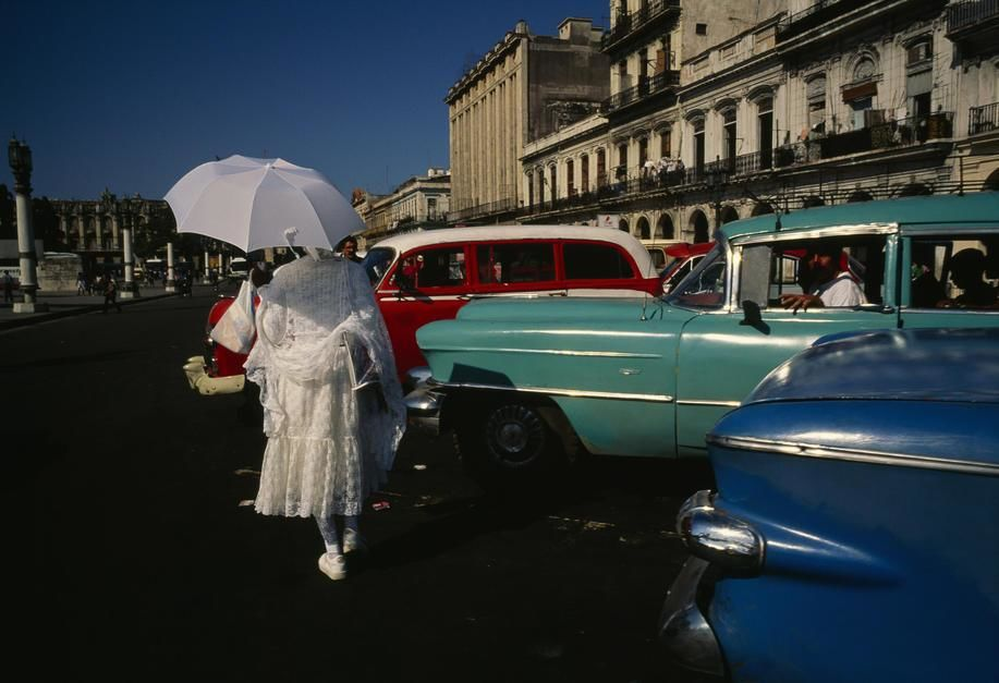 A woman in formal dress carrying an umbrella passes by vintage cars in Havana. [  -  2011]