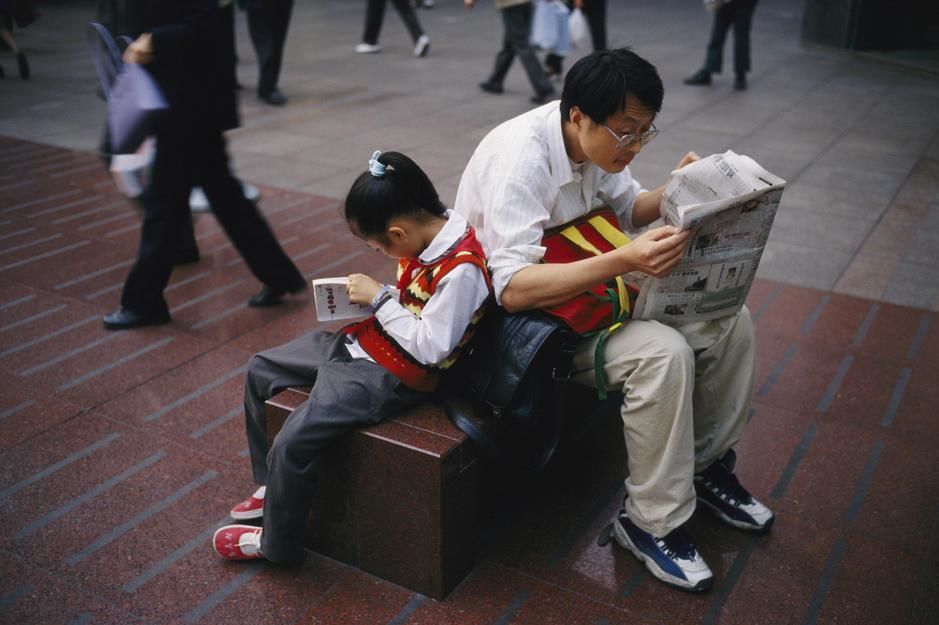 A man and his daughter lean against each other reading on Nanjing Lu, Shanghai. [  -  2011]