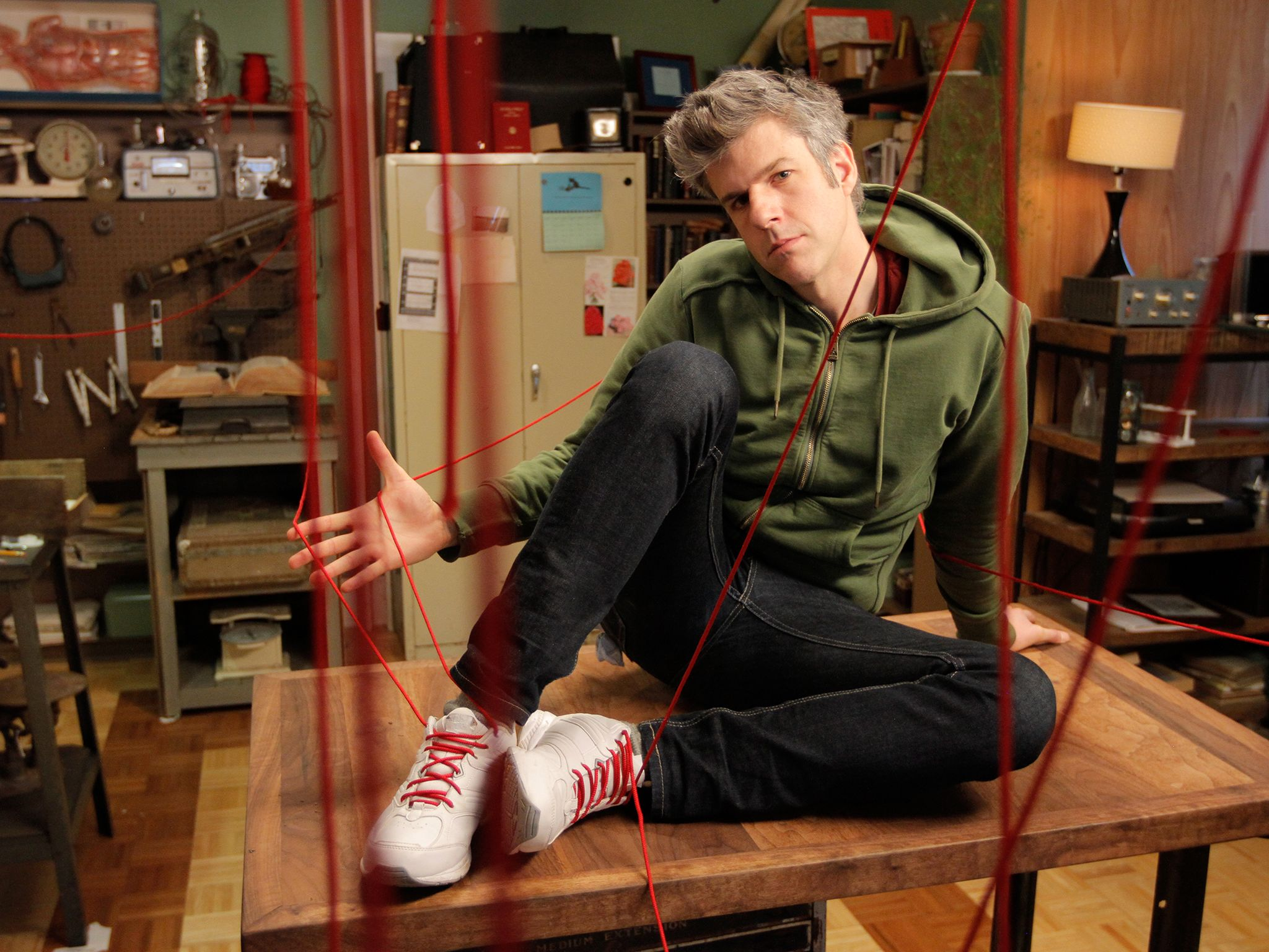 Beacon, NY: David Rees poses on top of his workbench with 50-foot laces strewn about his workshop... [Фото дня - Октябрь 2014]