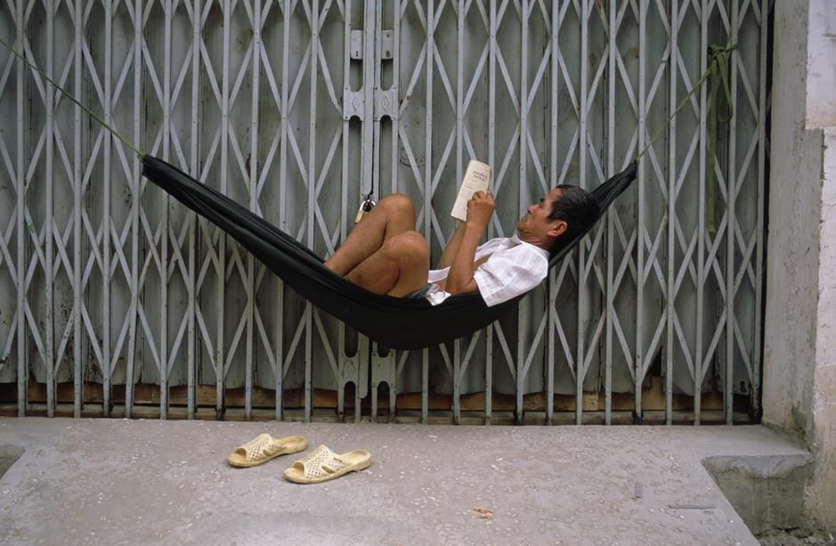 A man in a hammock reads a book outside the closed door of a shop in Saigon. [  -  2011]