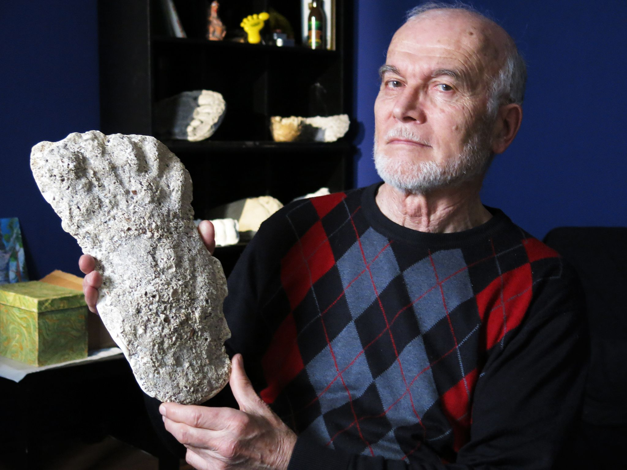 Moscow, Russia -  Igor Bourtsev holding up a Wildman footprint cast.