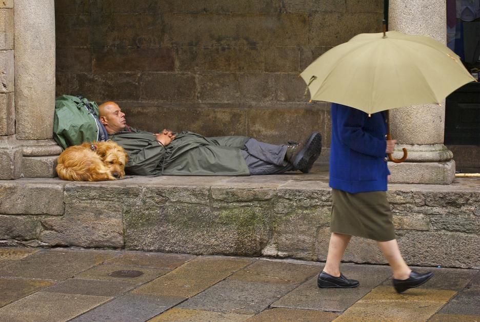 A woman carrying an umbrella passes a man on a pilgrimage sleeping in Santiago de Compostela, Gal... [  -  2011]