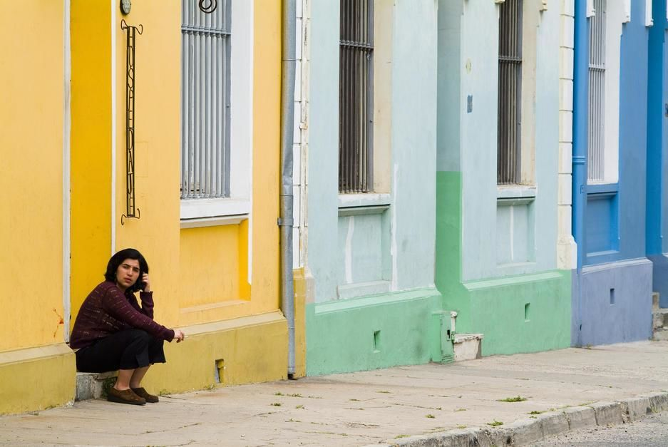 A woman sits on the stoop of an orange building in Valparaiso. [  -  2011]