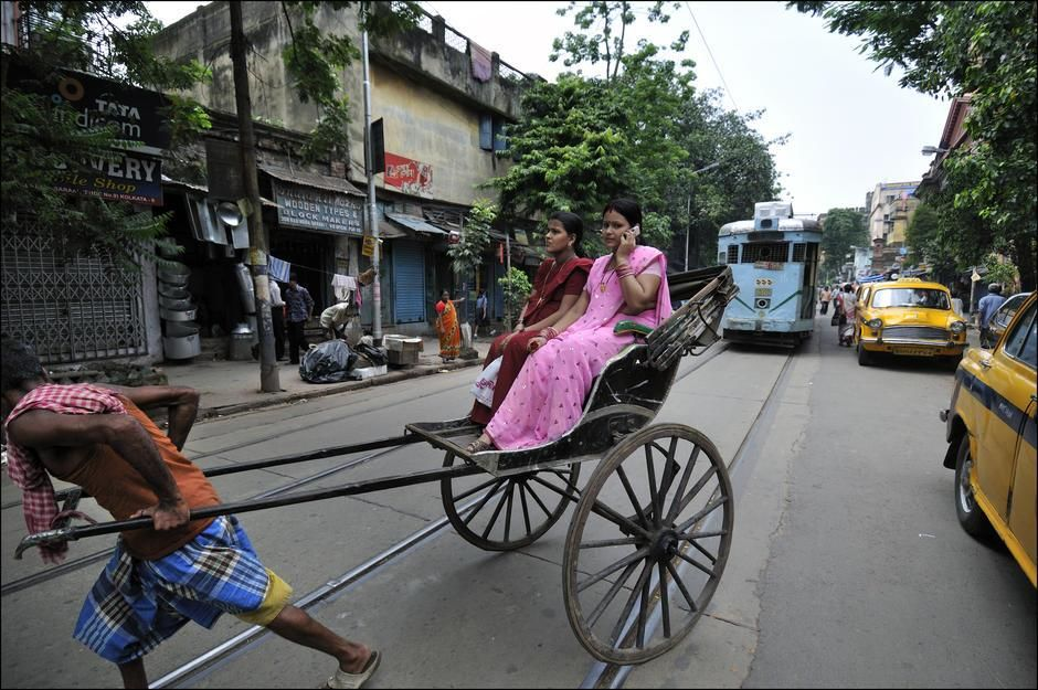 A woman talks on a mobile phone while riding a human-powered rickshaw in Kolkata, West Bengal. [  -  2011]