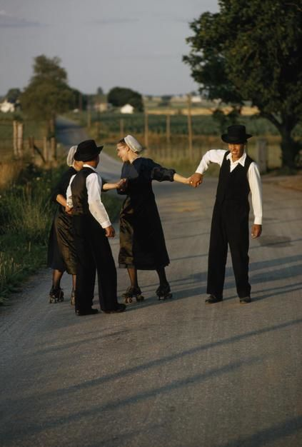 Amish-jongens trekken rolschaatsende vrouwen vooruit op een landweg in Lancaster, Pennsylvania.  [Photo of the day - april 2011]