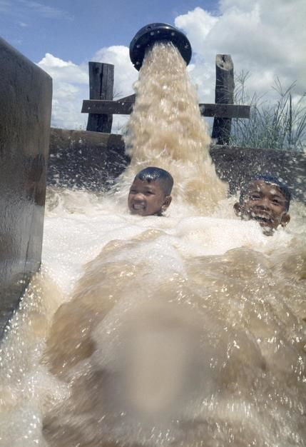 Boys laugh while being drenched with pumped Mekong River water. [Dagens foto - maj 2011]