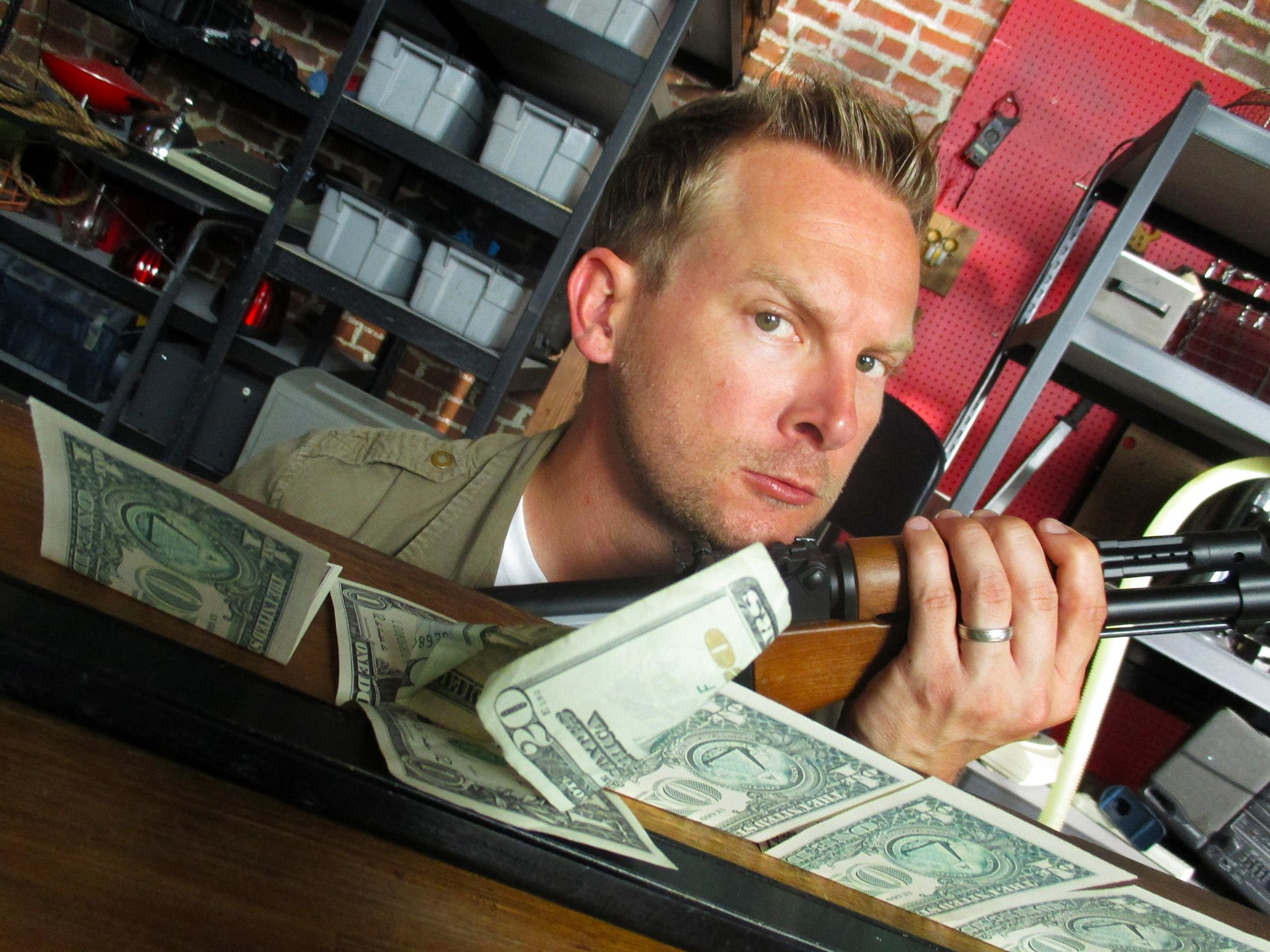 Los Angeles, CA.: In the workshop, Brian poses with a rifle next to a line of bills and a magnet.... [Photo of the day - april 2015]
