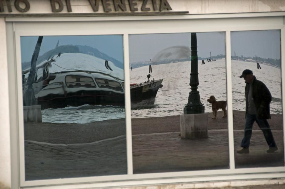 A boat and man walking his dog are reflected by a caf window in Venice. [Dagens billede - maj 2011]