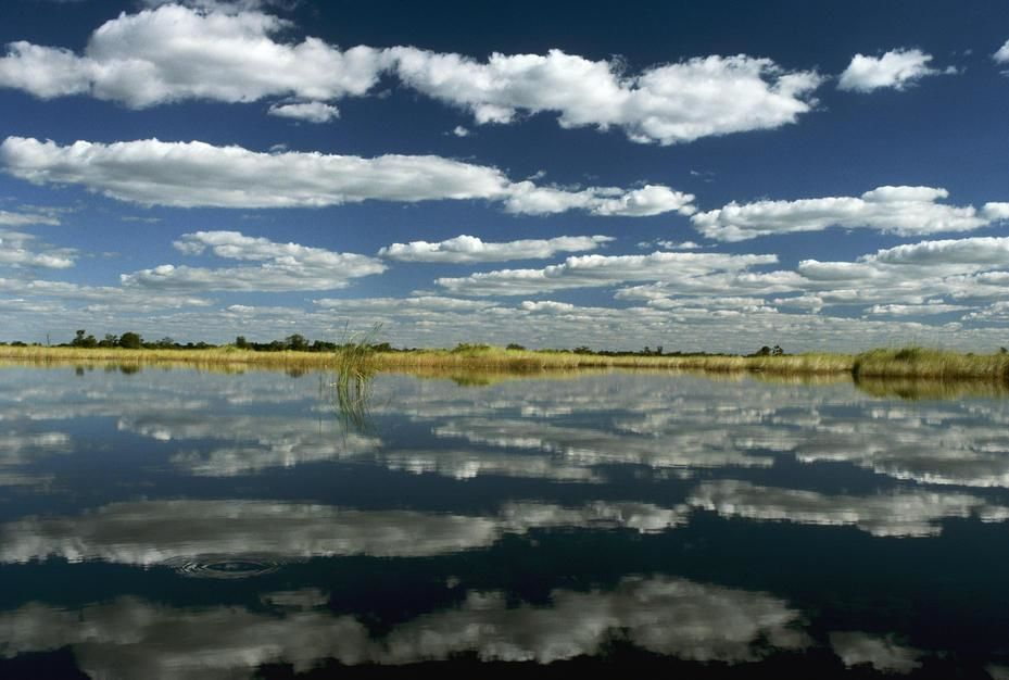 Clouds over the Okavango Delta reflect from Qogana Lagoon. Unlike the seasonally dry outer delta,... [Dagens foto - augusti 2011]