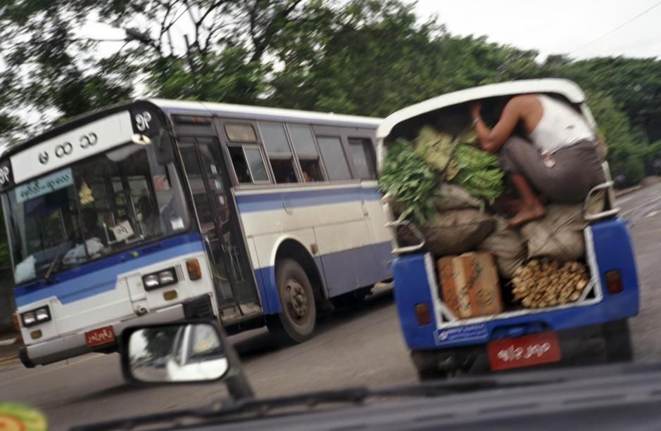A man crouches down inside the back of a truck carrying vegetables in Rangoon. [  -  2011]