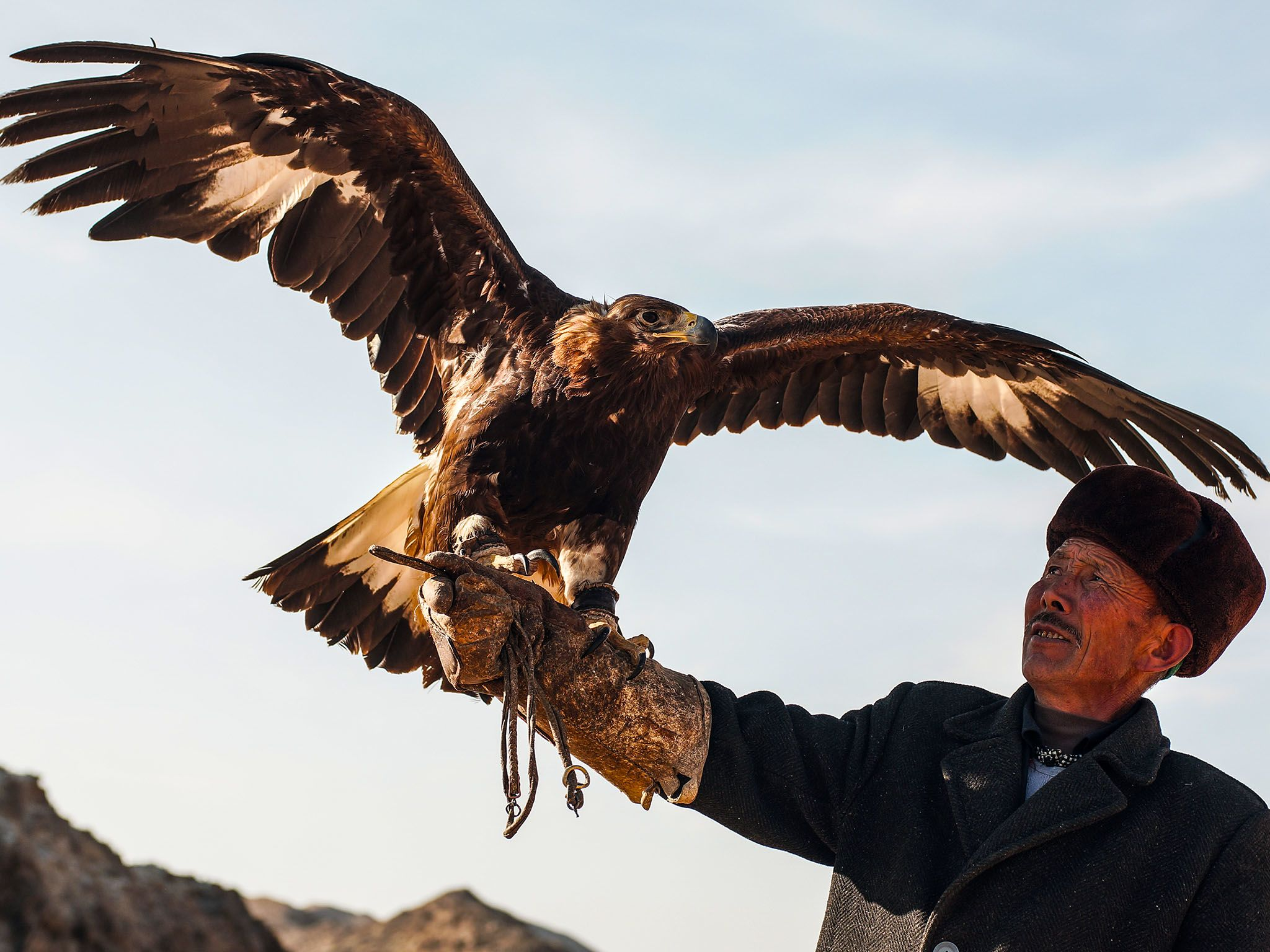 Macan and his eagle. Macan, a master falconer, teaches his son how to hunt with eagles amidst a r... [Фото дня - Август 2015]