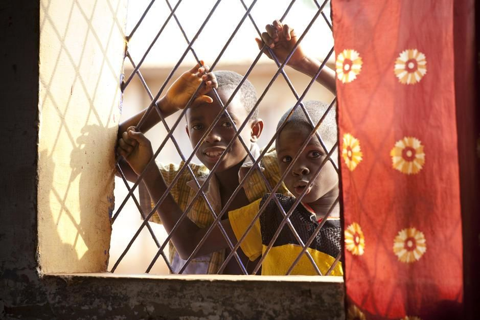 Two young boys peer through a bar window. [Photo of the day - May 2011]