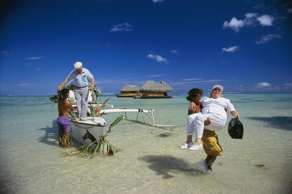 Local people help French tourists ashore after a lagoon cruise in an outrigger canoe on Tahiti Is... [Dagens foto - augusti 2011]