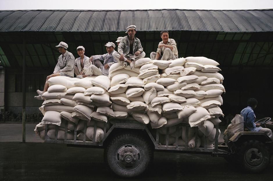 Men sit on bags of flour at a manufacturing plant in Hunan Province. [Foto do dia - Junho 2011]