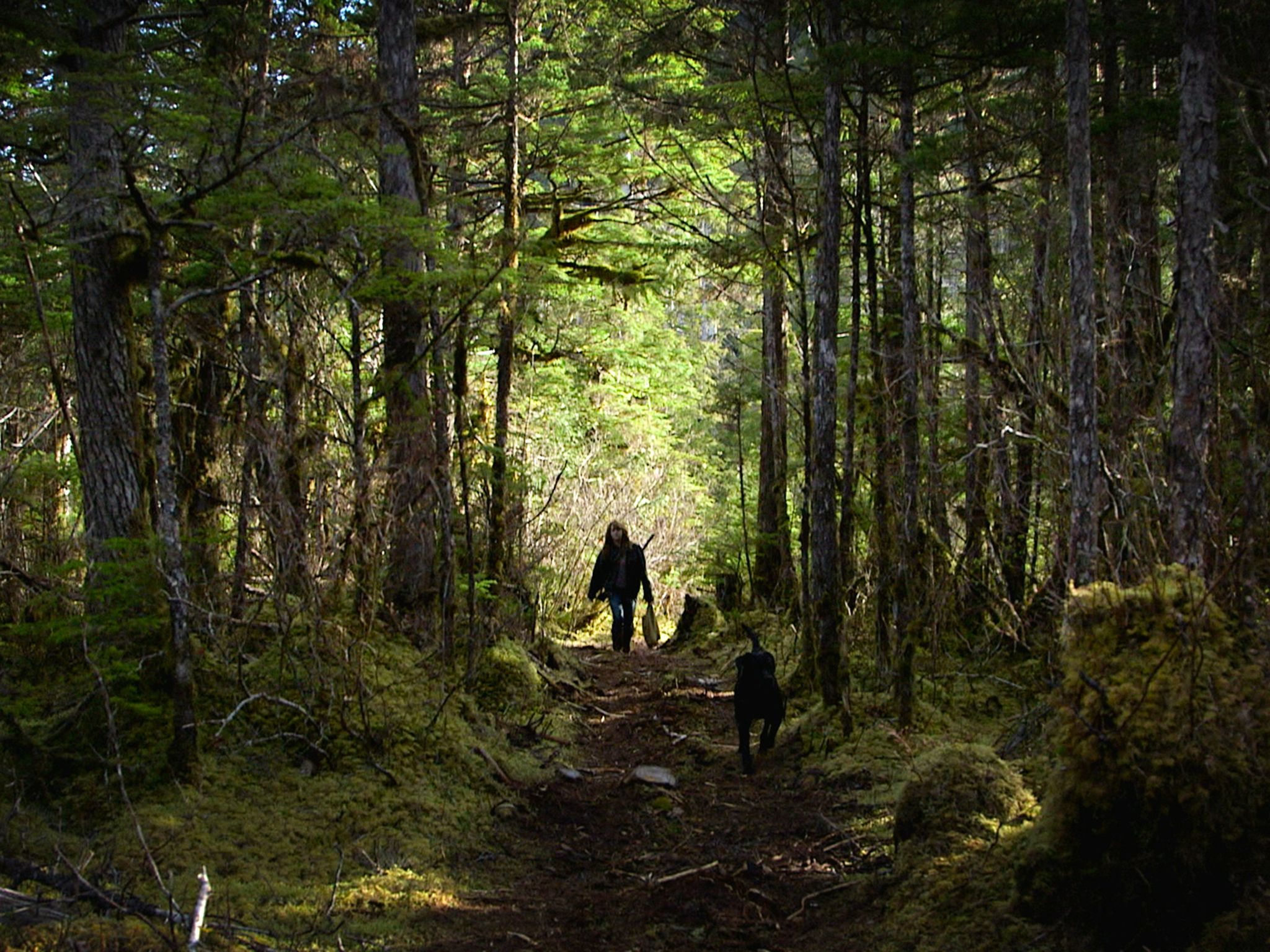 Port Protection, Alaska: Timbi walks through the woods with her dog, Smokey. This image is from... [Photo of the day - November 2015]