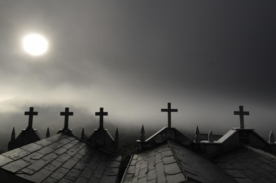 Sun shining through fog on Mausoleums in Galicia. [Photo of the day - ژوئن 2011]