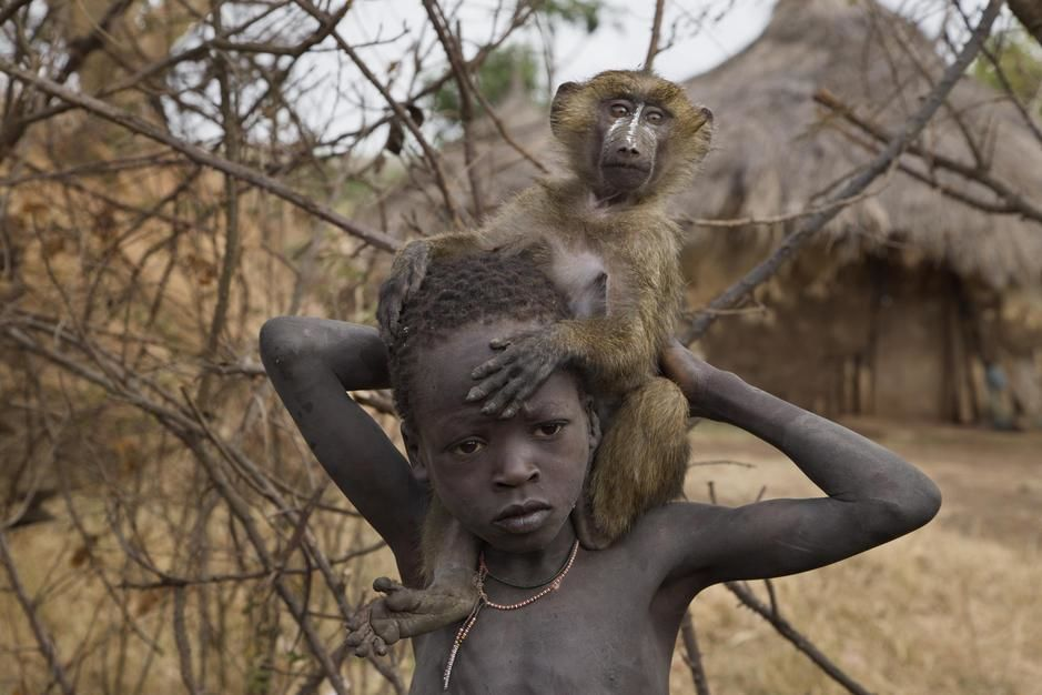 A boy and his pet baboon wander the Suri village of Tulgit. [Photo of the day - June 2011]
