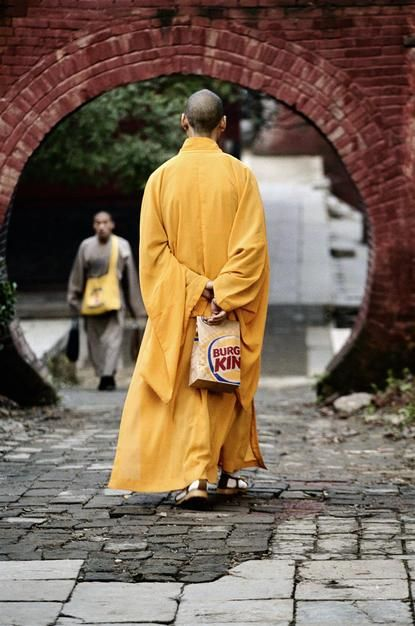 A monk at the Shaolin temple in Henan Province walks with a Burger King bag. [Foto do dia - Junho 2011]
