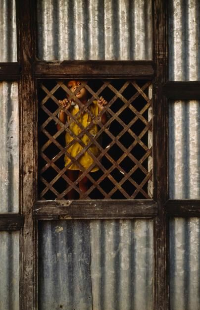 A young boy in a poor rural village looks through a lattice window. [תמונת היום - יוני 2011]