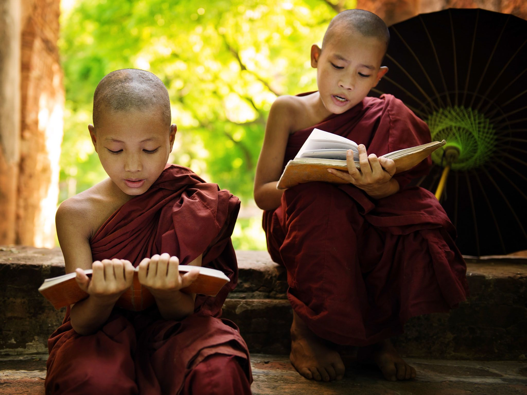 Southeast Asian Myanmar little monk reading book outside monastery, Buddhist teaching. This... [Photo of the day - April 2016]