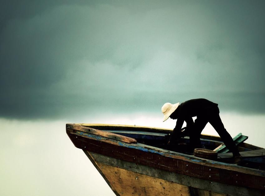 A worker doing his job on a ship before the heavy rains arrive. [Photo of the day - יוני 2011]