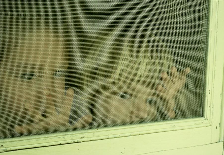Sisters behind a screen door in Park Rapis, Minnesota. [Fotografija dneva - julij 2011]